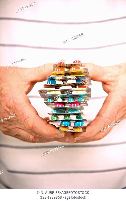 Senior hands close up holding a colored pile of pills and tablets symbol of over medication