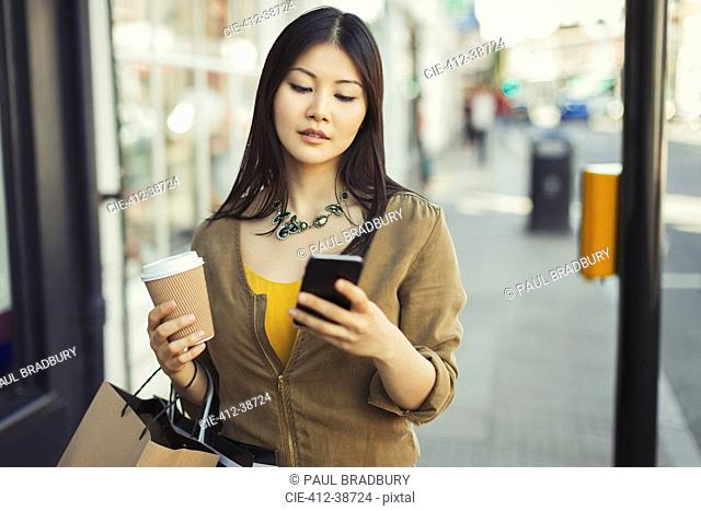 Young woman with coffee texting with cell phone on urban sidewalk