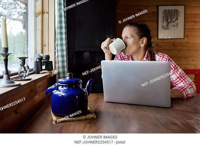 Woman at home looking through window