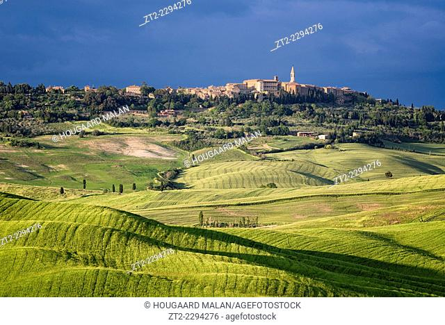 Landscape photo of the town of Pienza on a hilltop above rolling farmlands. Val D'Orcia, Tuscany, Italy