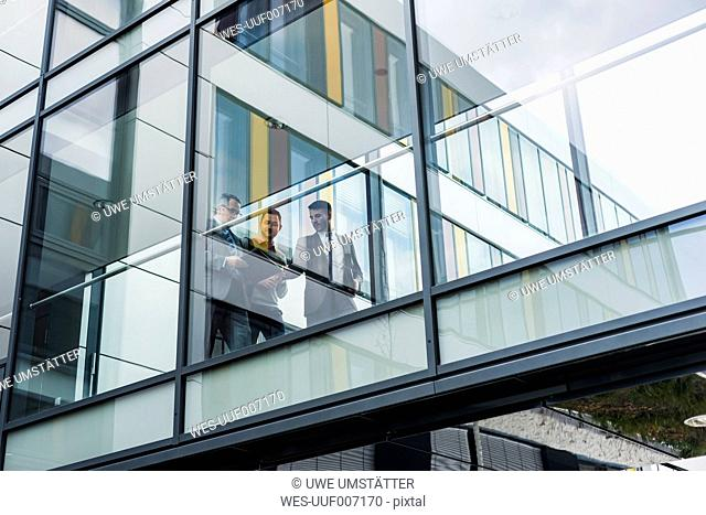 Three businessmen behind glass facade, passage