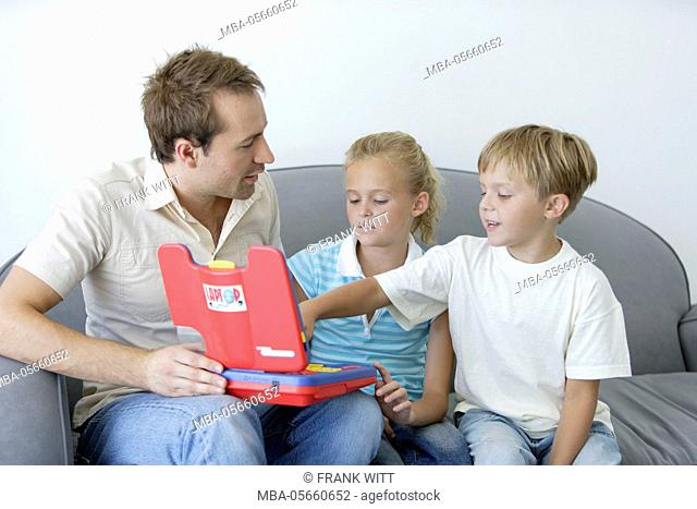 Father and 2 children with toys laptop on sofa