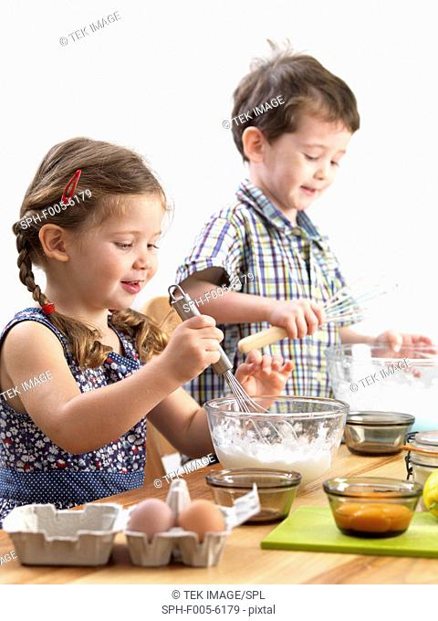 MODEL RELEASED. Young children baking. Three year old twins baking