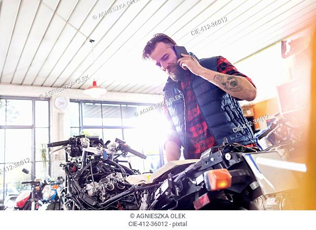 Motorcycle mechanic talking on cell phone in workshop