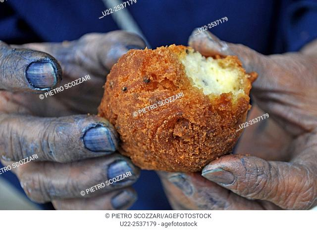 Nago, Okinawa, Japan: a woman with blue hands holding a sata andagi, traditional Okinawan sweet. Her hands are blue because she just colored handkerchieves to...