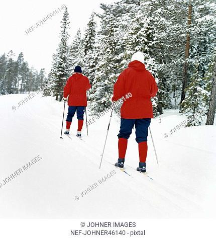Elderly couple skiing in the woods