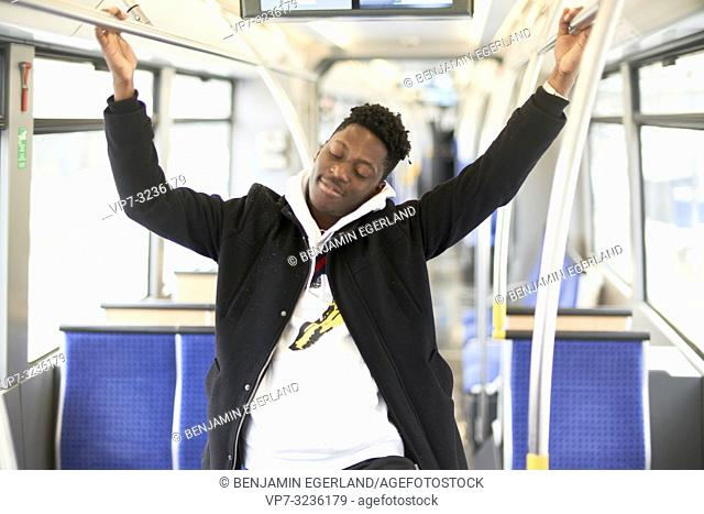 young man in tram, public transport, sleepy tired, in Munich, Germany