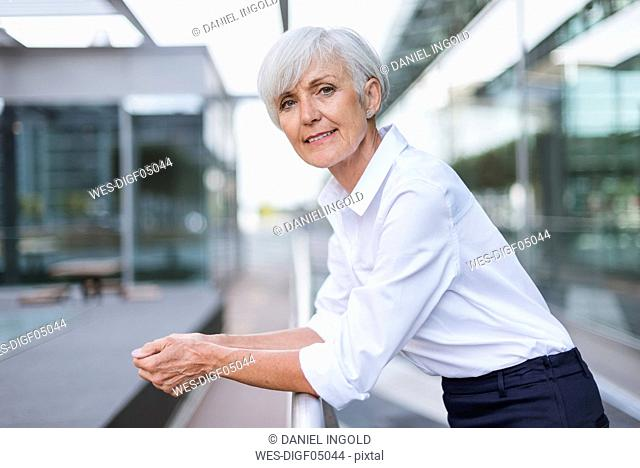 Portrait of confident senior woman leaning on railing in the city