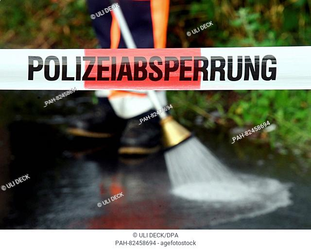The ground is cleaned of the pool of blood at the crime scene behind police tape written with 'police cordon' in Rheinstetten, Germany, 03 August 2016