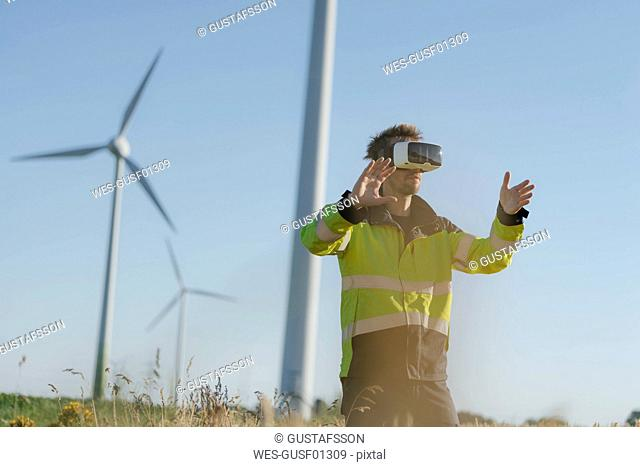 Engineer standing in a field at a wind farm wearing VR glasses