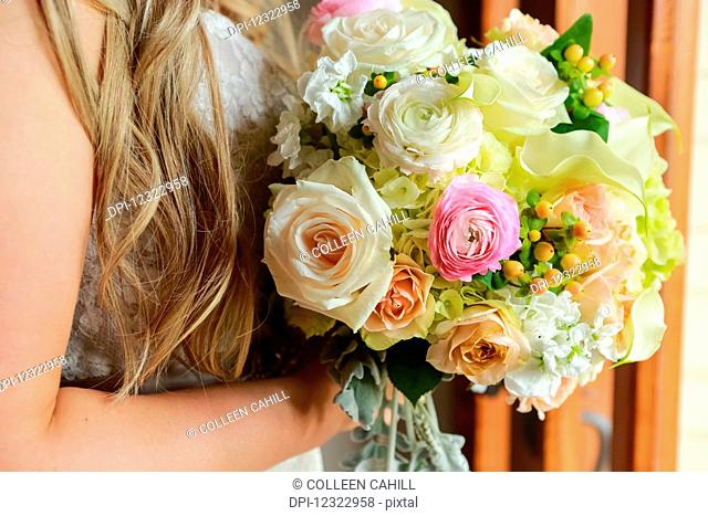 Portrait of a bride with long, blond hair and a flower bouquet; Oregon, United States of America