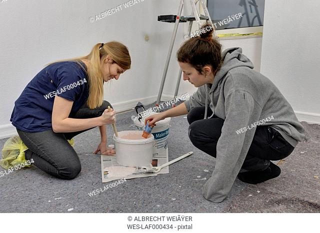 Two friends mixing colours for painting