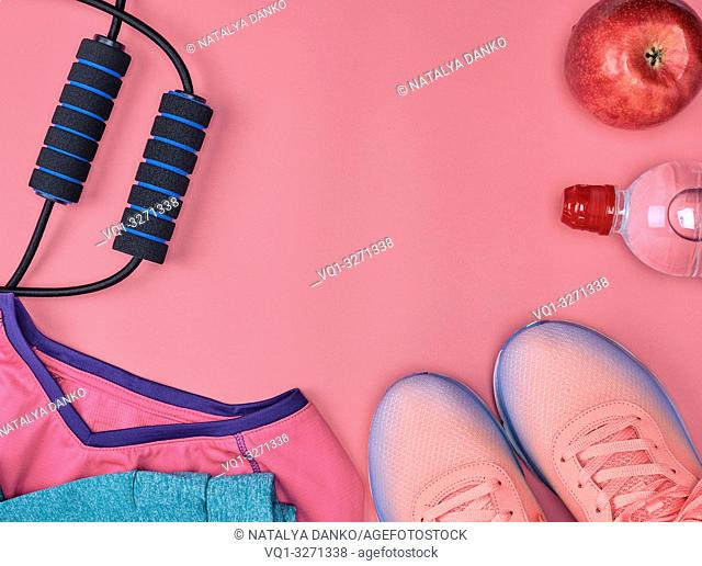 sport textile shoes and other items for fitness on a pink background, top view, copy space
