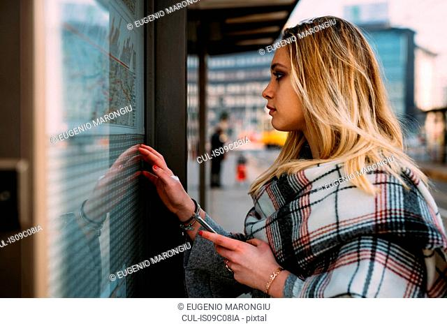 Young woman looking at timetable at tram station, Milan, Italy