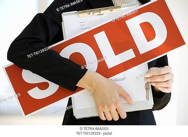 Real Estate agent holding clipboard and Sold sign