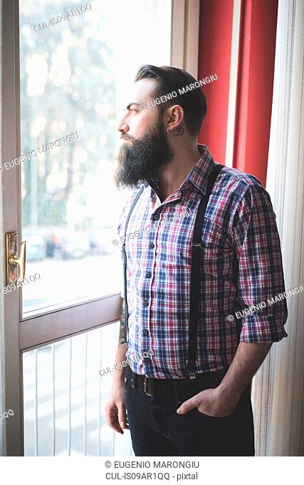 Young bearded man in braces looking out of door