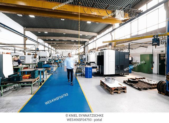 Businessman walking through factory workshop