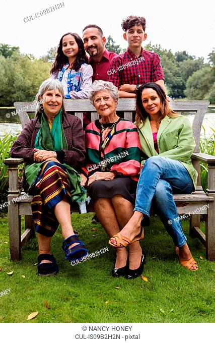Portrait of four generation family, beside lake, smiling