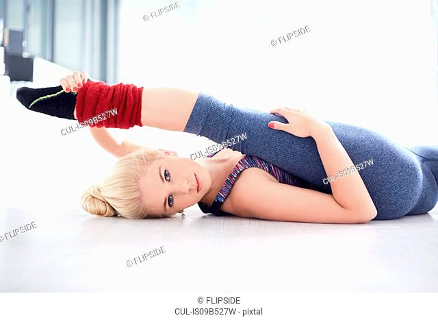Portrait of young female ballet dancer practicing in dance studio, lying on back