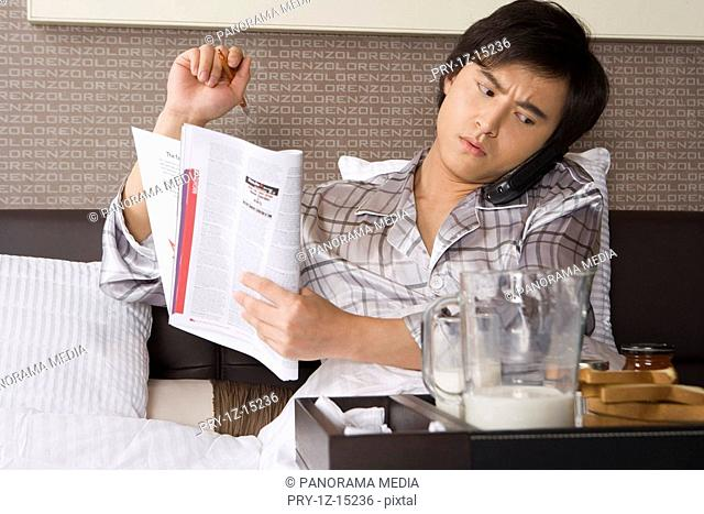 Young man using cordless phone and holding newspaper