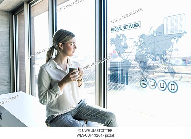 Young businesswoman looking at virtual world map at window pane in office