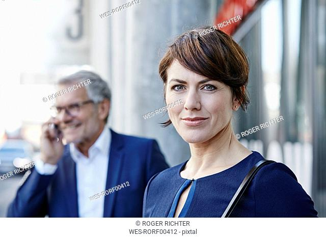 Portrait of businesswoman with businessman on the phone in background