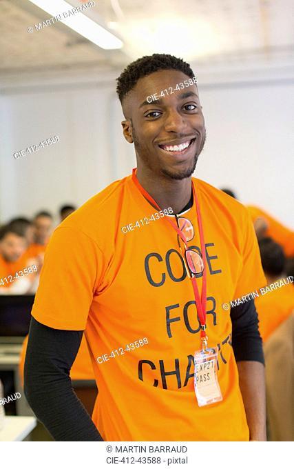 Portrait confident hacker coding for charity at hackathon
