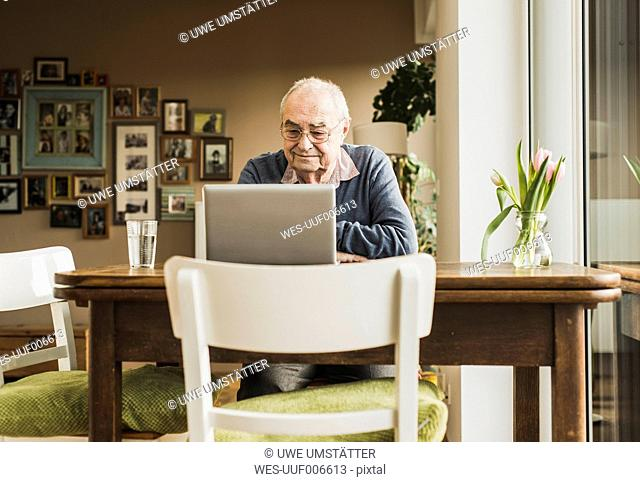 Senior man sitting at table in the living room using laptop