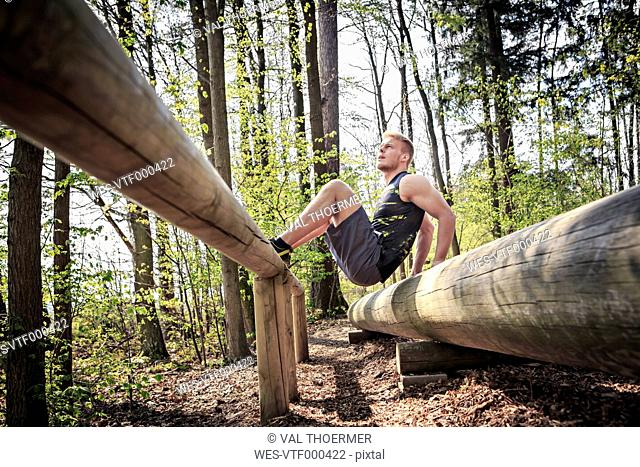 Germany, Coburg, Young man at training on a fitness trail in a forest