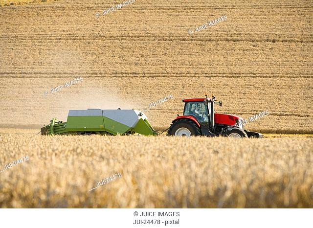 Tractor and straw baler in sunny, rural field