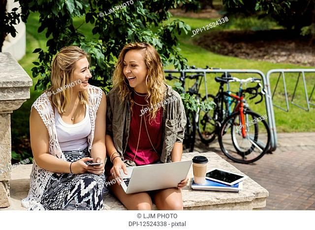 Two female university students laughing and talking together while using their technology outside on the campus; Edmonton, Alberta, Canada