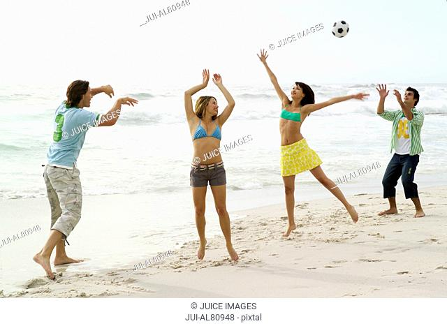 Friends playing with soccer ball at beach
