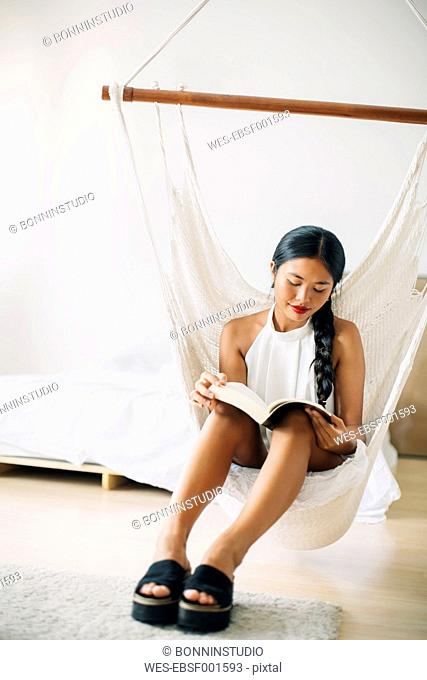 Young woman sitting in hammock reading book