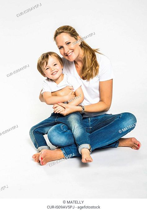 Studio portrait of mid adult woman sitting on floor with son