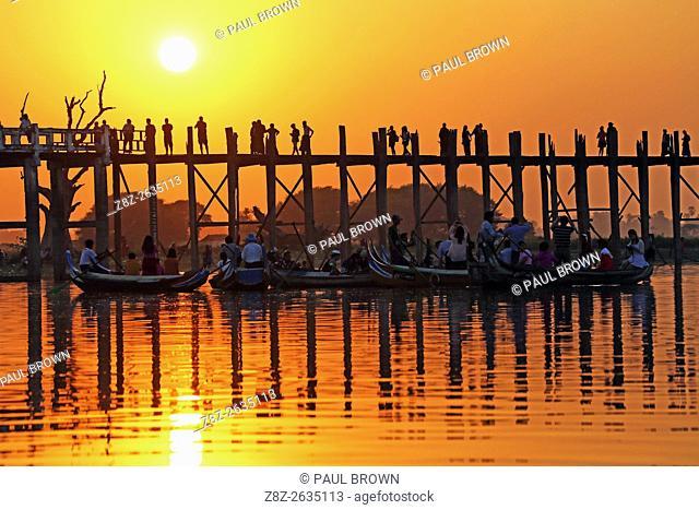 People crossing the U Bein Bridge across the Taungthaman Lake at sunset in Amarapura, Mandalay, Myanmar (Burma) believed to be the oldest and longest teakwood...