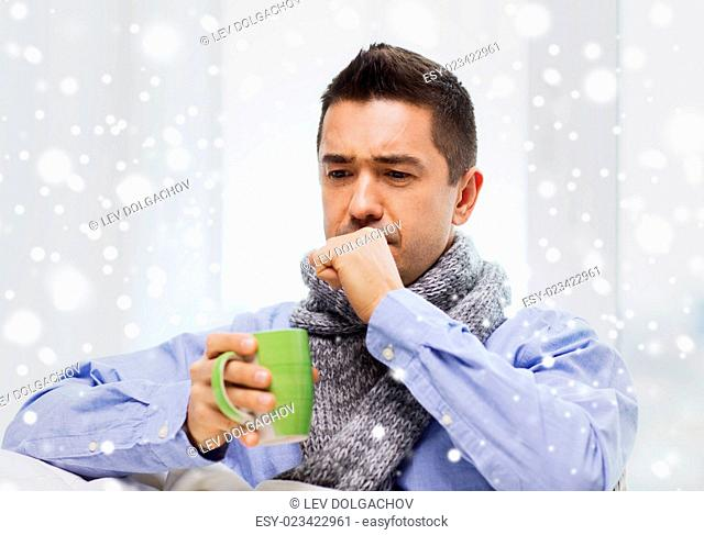 healthcare, people and medicine concept - ill man with flu coughing and drinking hot tea from cup at home over snow effect