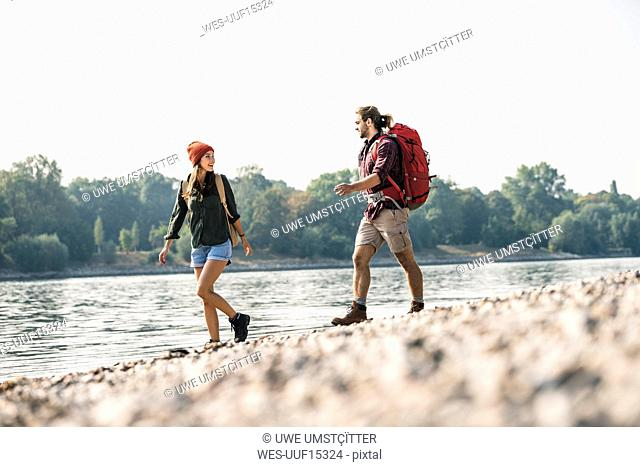 Young couple with backpacks walking at the riverside