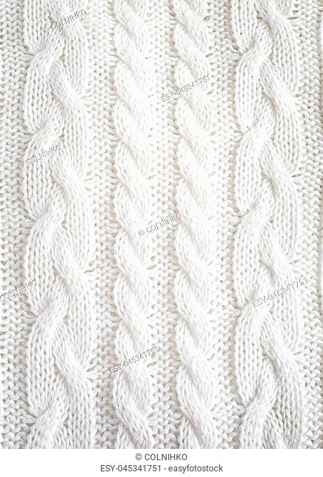 Knitted white texture with a pattern of braids