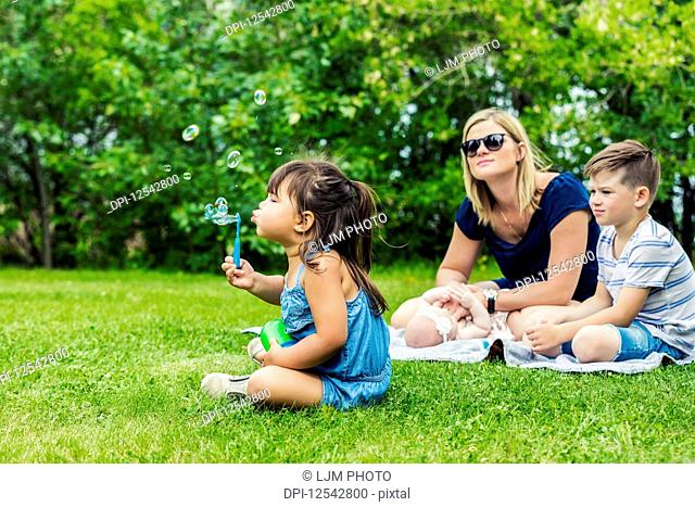 A young mother watching her daughter blowing bubbles while sitting on a blanket with her baby and her son in a city park on a warm sunny day; Edmonton, Alberta