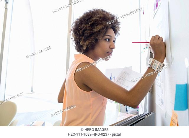 Businesswoman writing on whiteboard in office