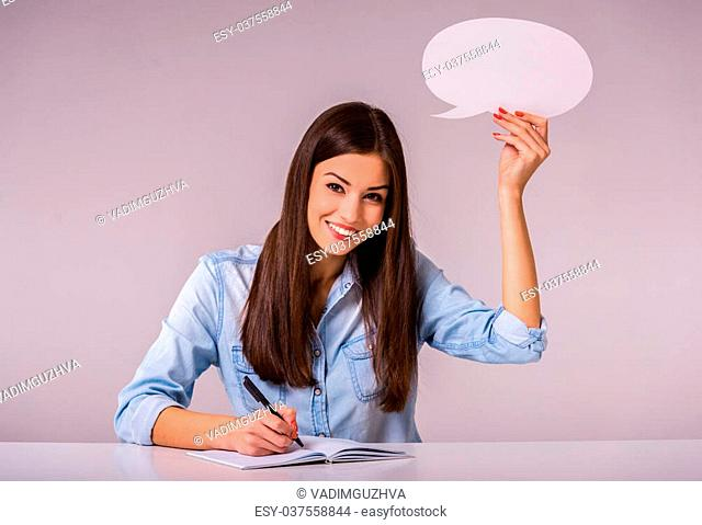 Beautiful young girl sitting at a desk and writing in a notebook, holding empty text bubble. Grey background