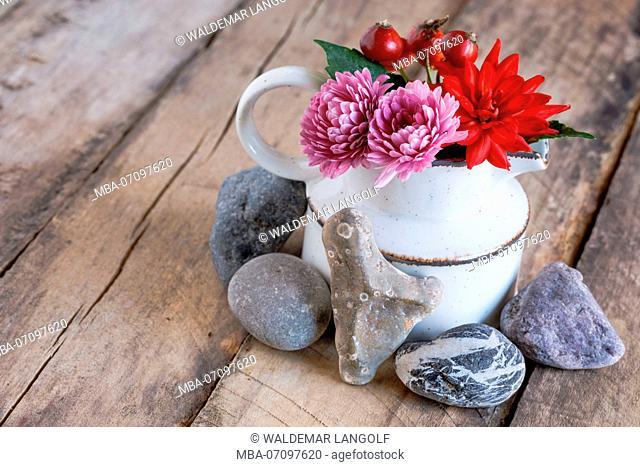 Autumnal arrangement, close-up, heart made of stone, wooden ground