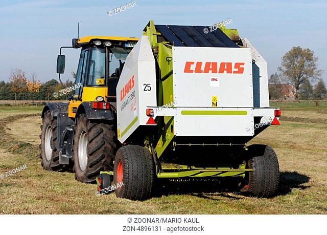 Ein Traktor vom Typ JCB Fastrac 3190 Plus mit einer Rundballenpresse vom Typ CLAAS Variant 280 bei der Heuernte auf einem Feld bei Dautschen in Sachsen