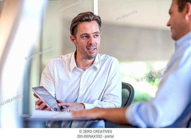 Male designer explaining idea on digital tablet at design office
