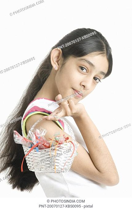 Portrait of a girl holding a basket of candy