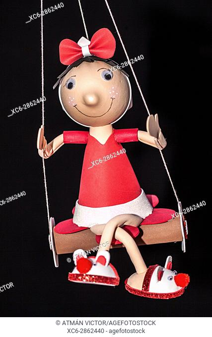 handmade wooden dressed girl doll on a swing