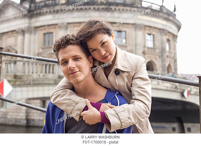Low angle portrait of woman embracing male friend against Bode Museum, Berlin, Germany