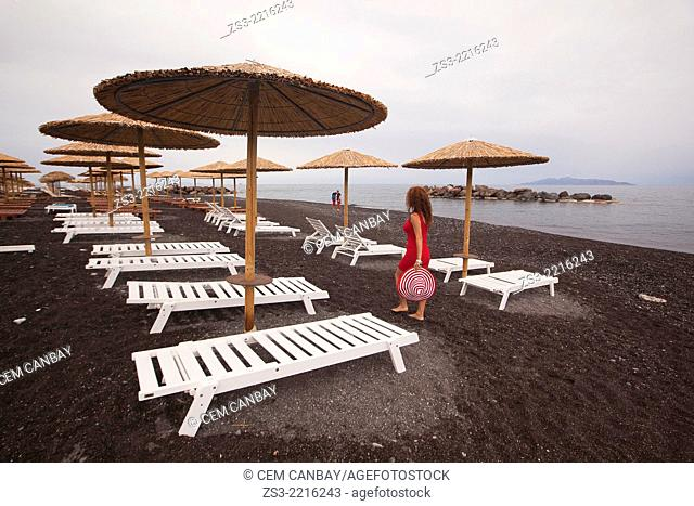 Thatched parasols and tourists in Kamari beach, Santorini, Cyclades Islands, Greek Islands, Greece, Europe