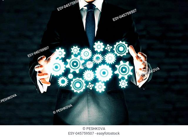 Teamwork concept with businessman in suit holding abstract gears on dark brick background