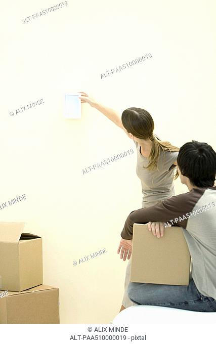 Woman hanging picture frame on wall, man watching, holding cardboard box
